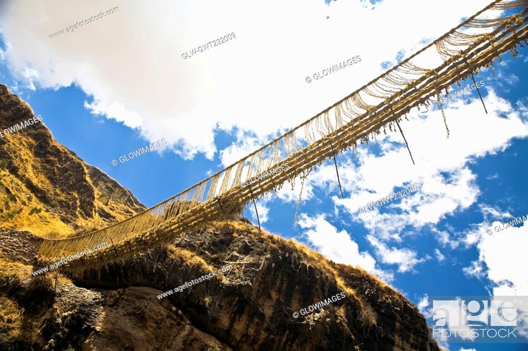 Stock Photo: Low angle view of a rope bridge across a mountain, Queswachaca, Peru.