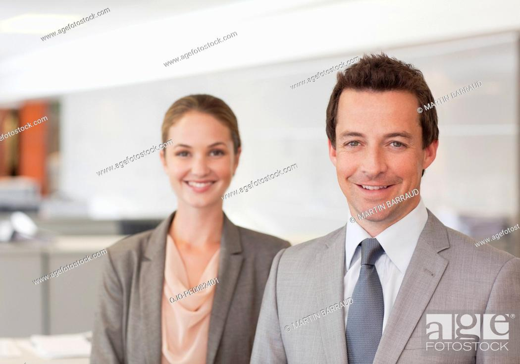 Stock Photo: Portrait of smiling businessman and businesswoman in office.