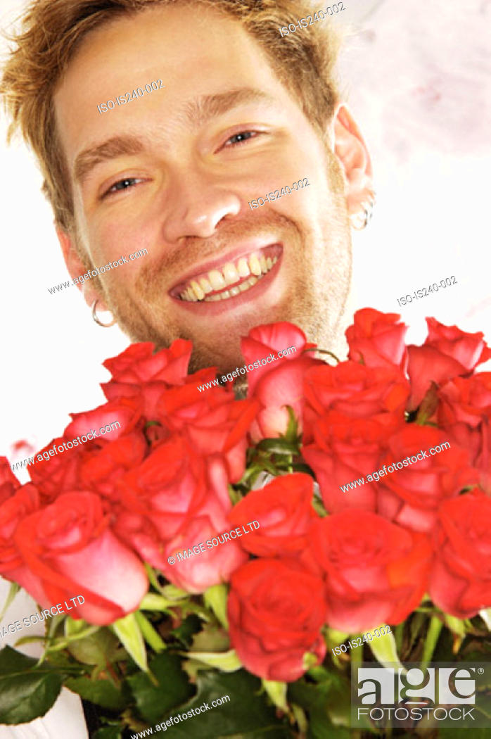 Stock Photo: Smiling man holding red roses.