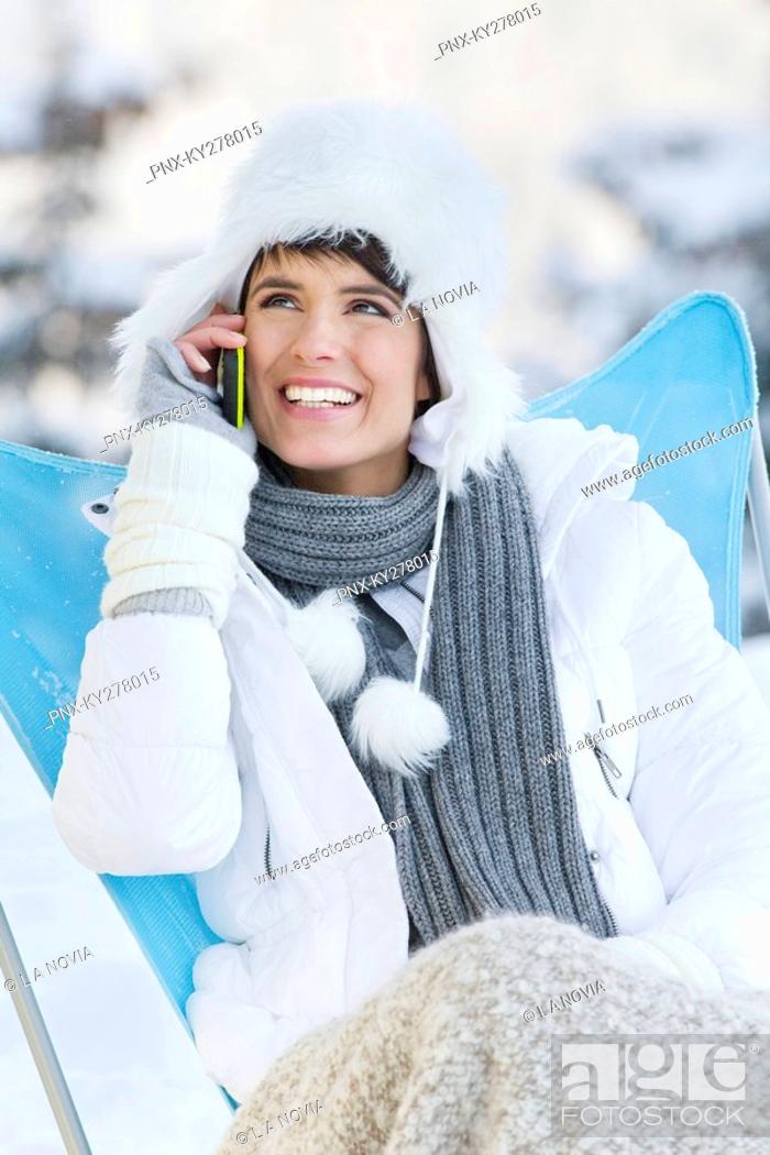 Stock Photo: Young woman using mobile phone in snow.