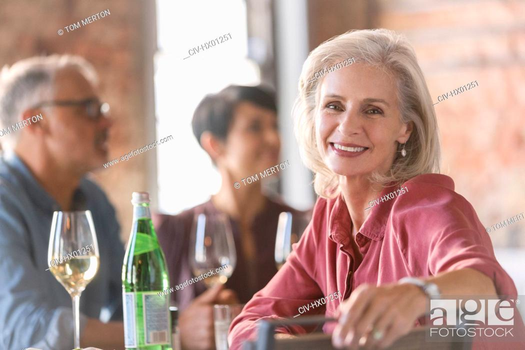 Stock Photo: Portrait smiling senior woman dining with friends in restaurant.