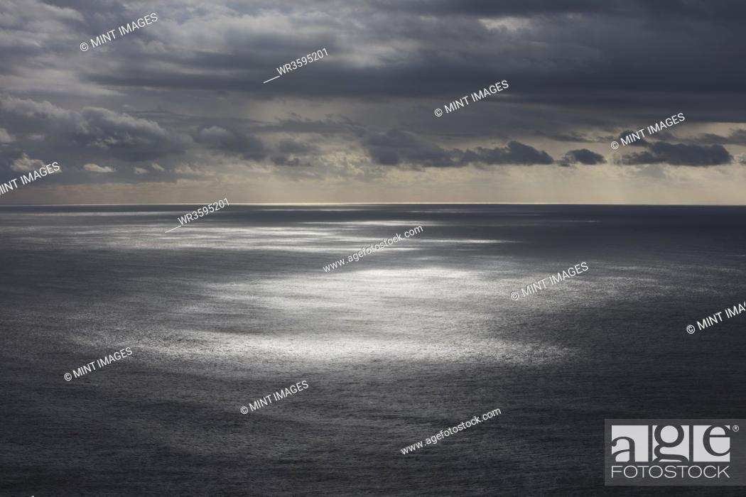 Stock Photo: Storm clouds clearing over expansive ocean, dappled sunlight on water, northern Oregon coast.