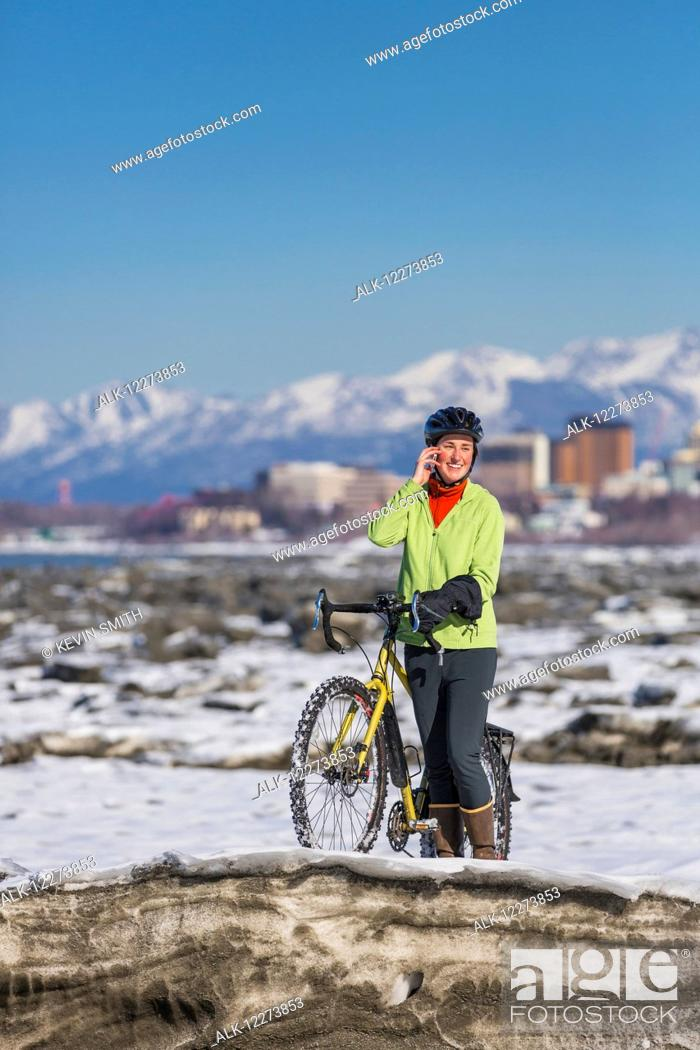 Stock Photo: Young woman with her bicycle talks on a cell phone while standing on frozen ice chunks along the Tony Knowles Coastal Trail, Anchorage, Southcentral Alaska.