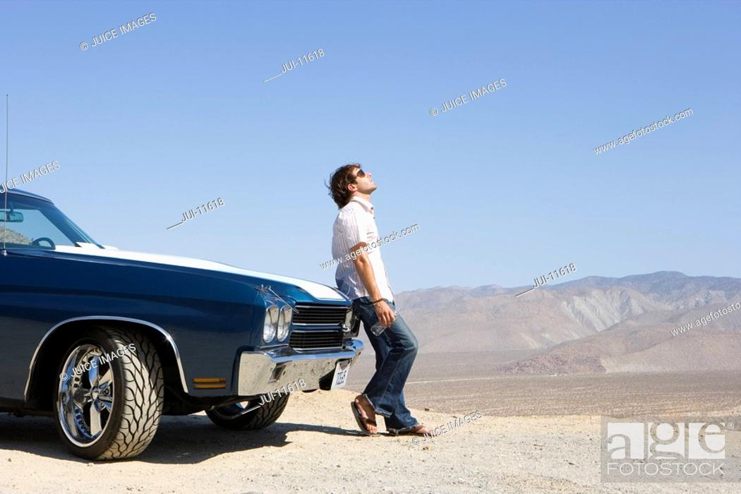 Stock Photo: Young man with water bottle in sunglasses by car in desert, looking up, side view.