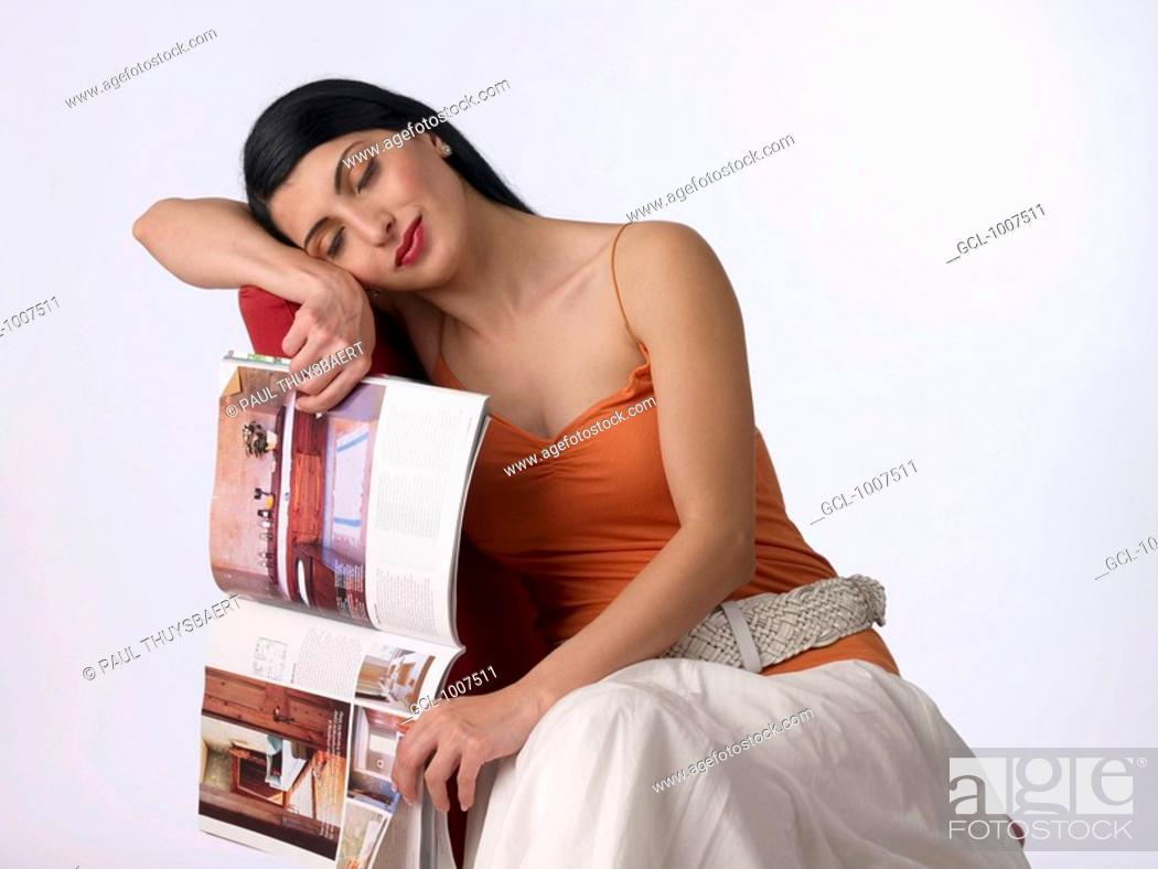 Stock Photo: Portrait of a woman with eyes closed and holding a magazine.