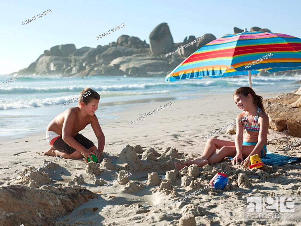Stock Photo: Boy and girl making sandcastles on beach.
