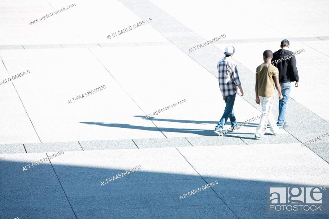 Stock Photo: Young men walking together across public square.