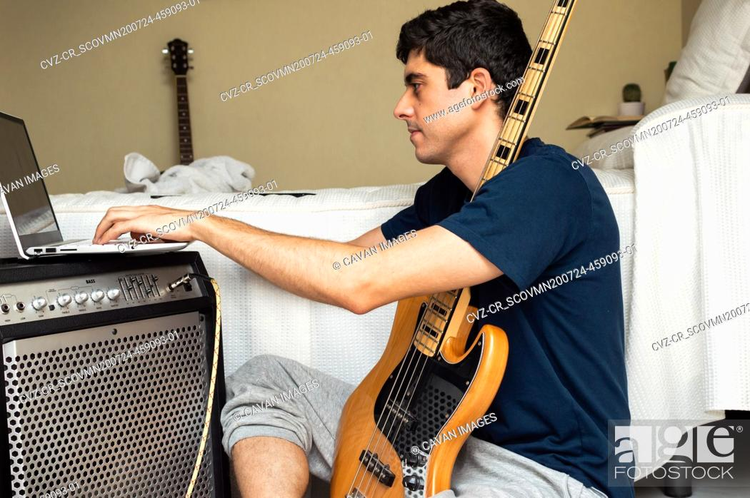 Imagen: Casual man using a laptop to learn to play electric bass at home.