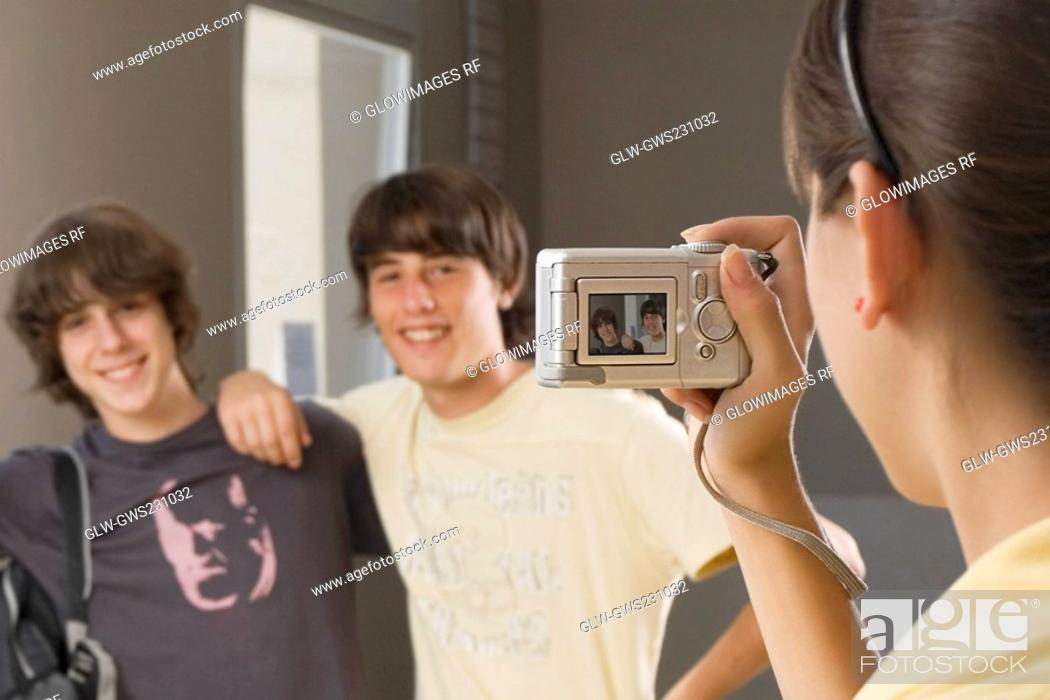 Stock Photo: Close-up of a teenage girl taking a photograph of her two friends with a digital camera.