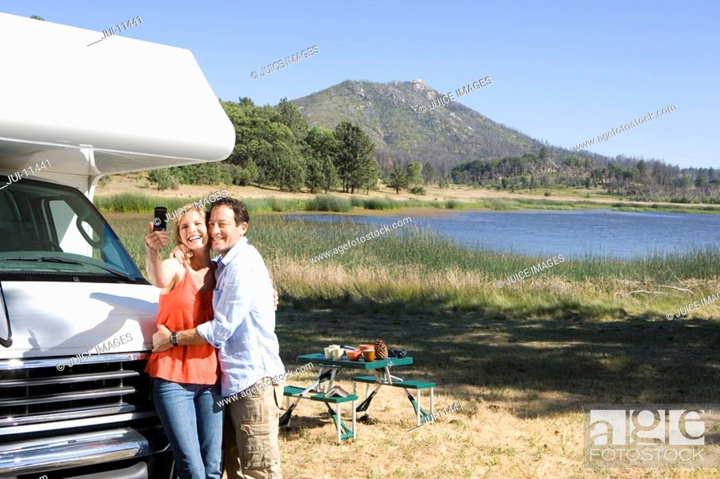 Stock Photo: Couple by lake and motor home taking photograph of themselves with mobile phone.