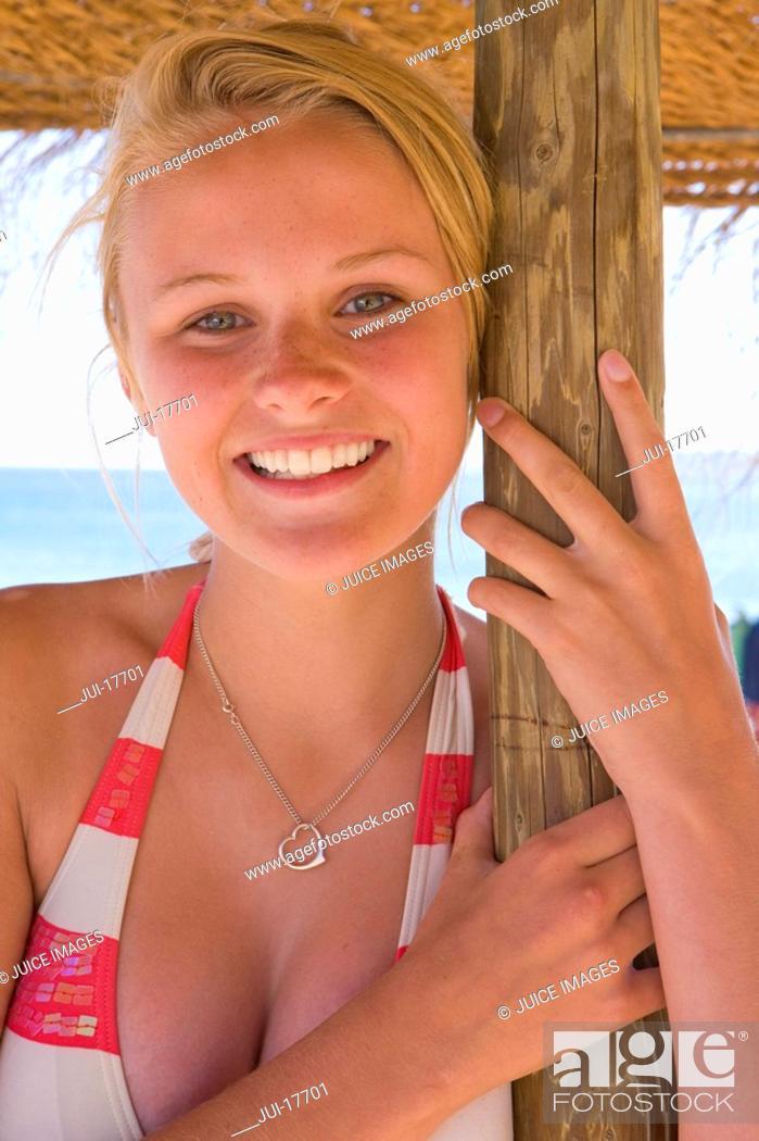 Stock Photo: Teenage girl posing under beach umbrella.