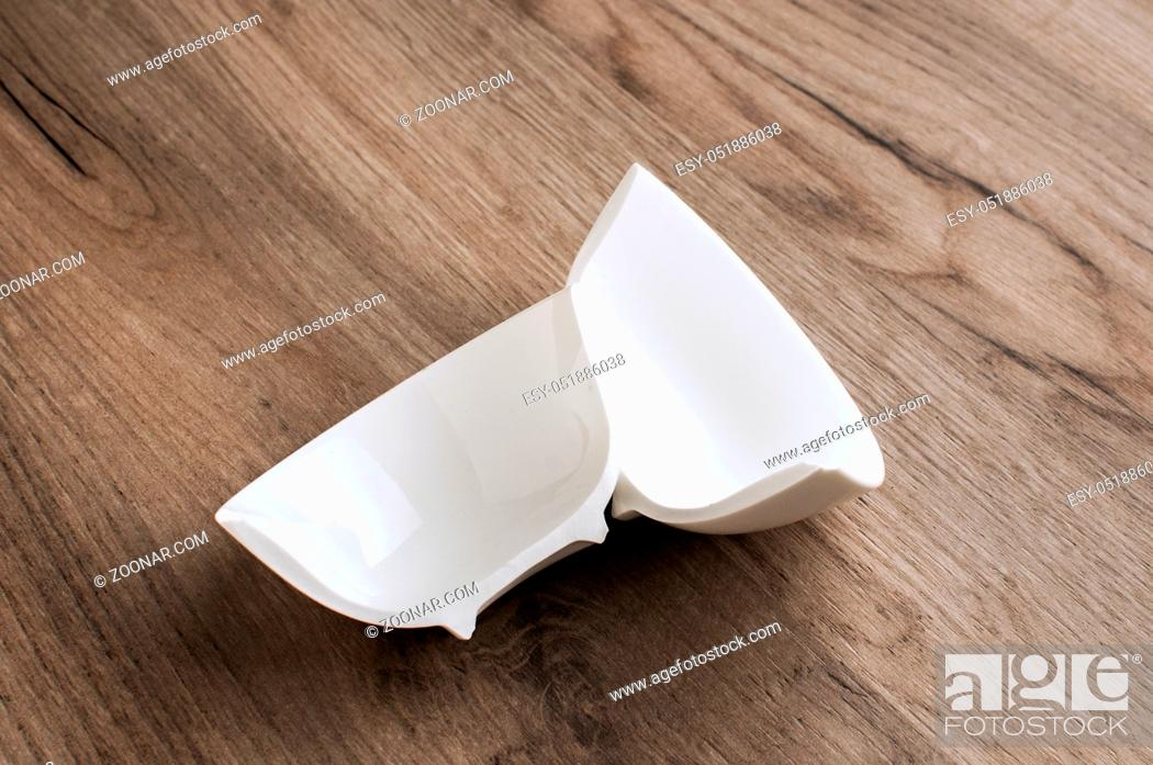 Stock Photo: Broken in two halves small white porcelain bowl closeup on wooden board background.