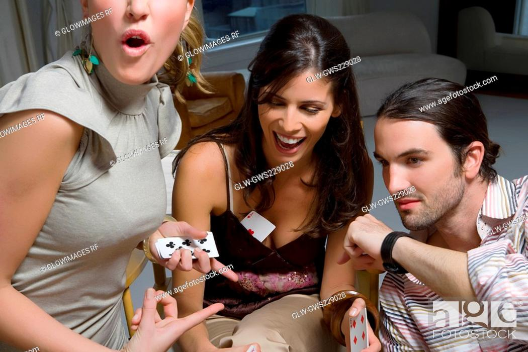 Stock Photo: Two young women with a young man playing cards.