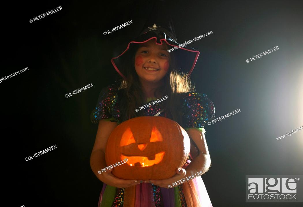 Stock Photo: Portrait of girl wearing halloween witch costume holding pumpkin.