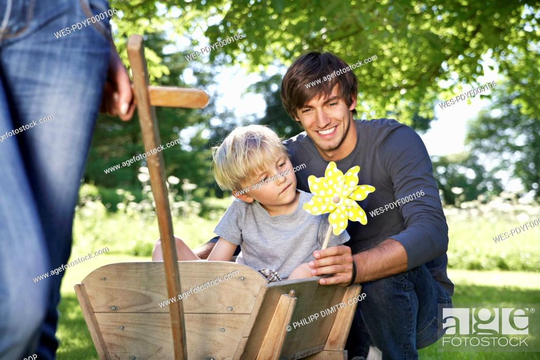 Stock Photo: Germany, Cologne, Father and son with paper windmill, smiling.