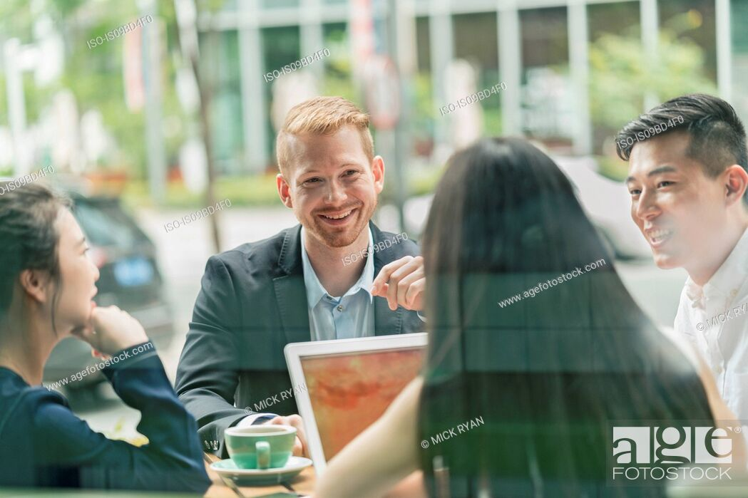 Photo de stock: Group of businesspeople, having meeting at cafe, using laptop, outdoors.
