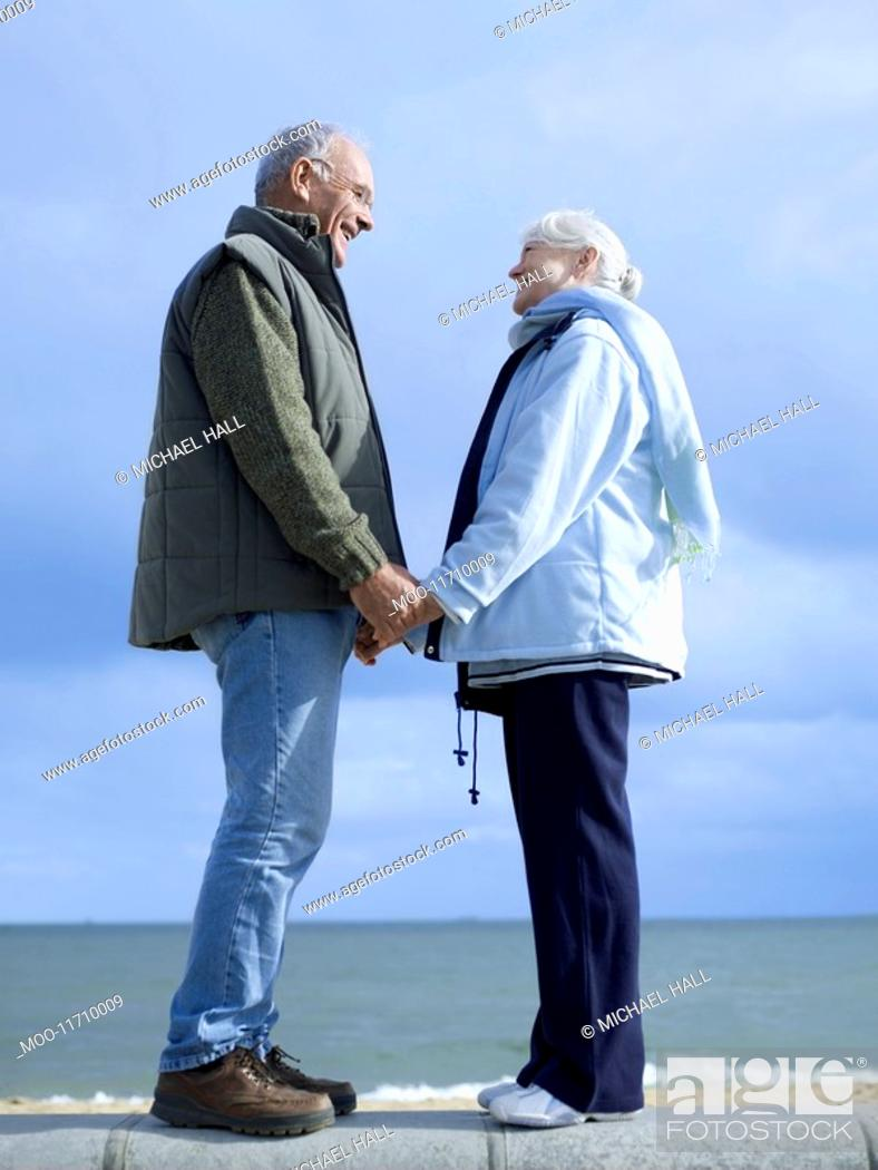 Stock Photo: Senior couple standing on wall by water holding hands.
