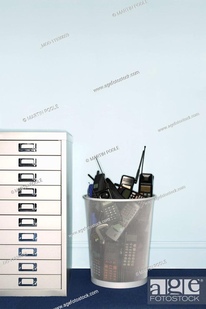 Stock Photo: Mobile phones in trash can by filing cabinet.