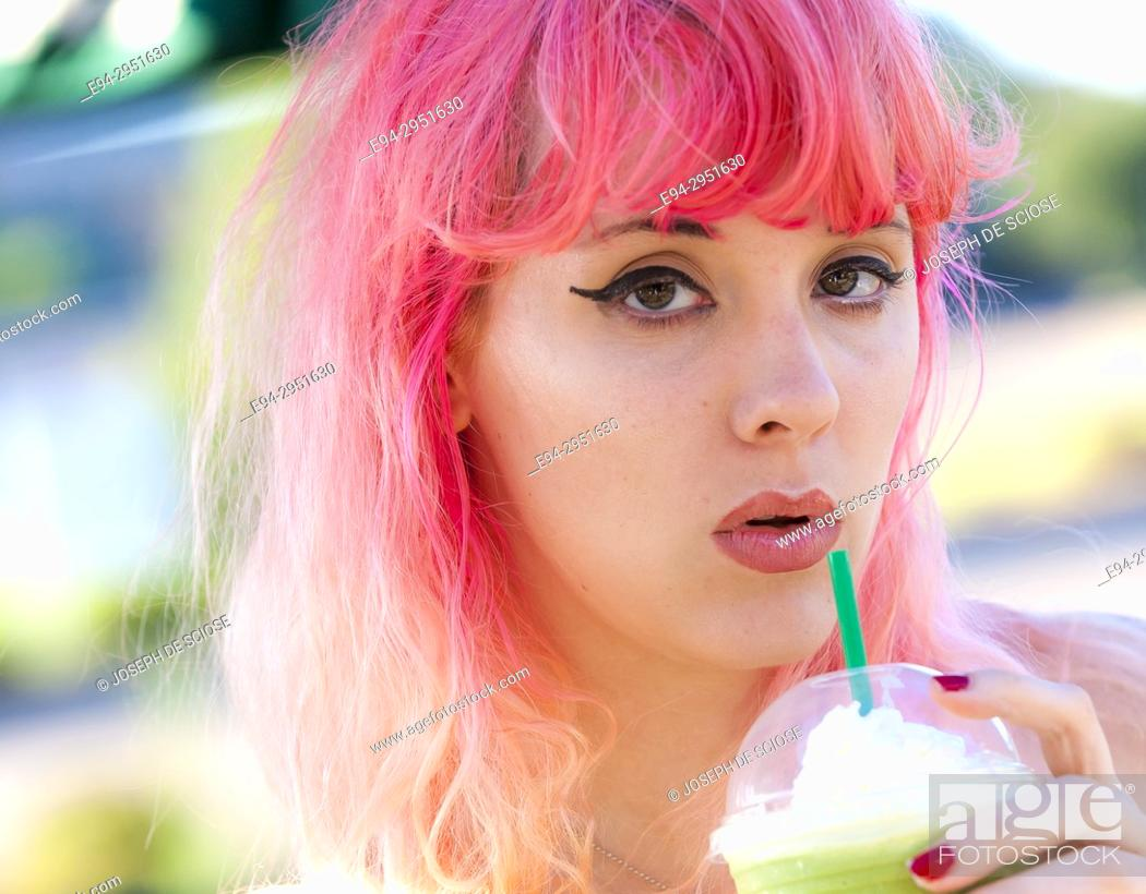 Stock Photo: A 25 year old woman with pink hair, looking at the camera and holding a cold drink too her mouth, outdoors.