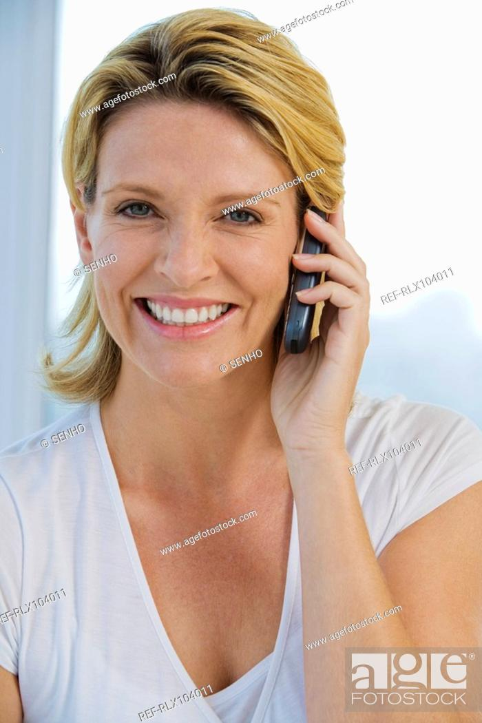 Stock Photo: Mature woman smiling while using Cell phone, looking straight at camera.