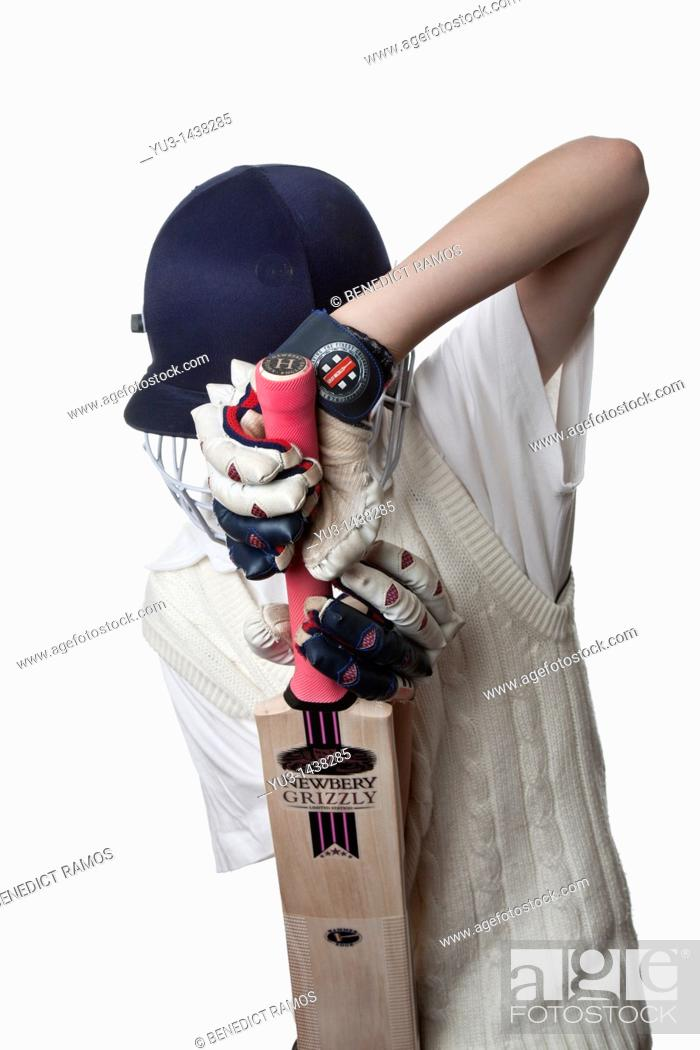 Stock Photo: Young cricketer in protective helmet and gloves demonstrating a defensive shot.