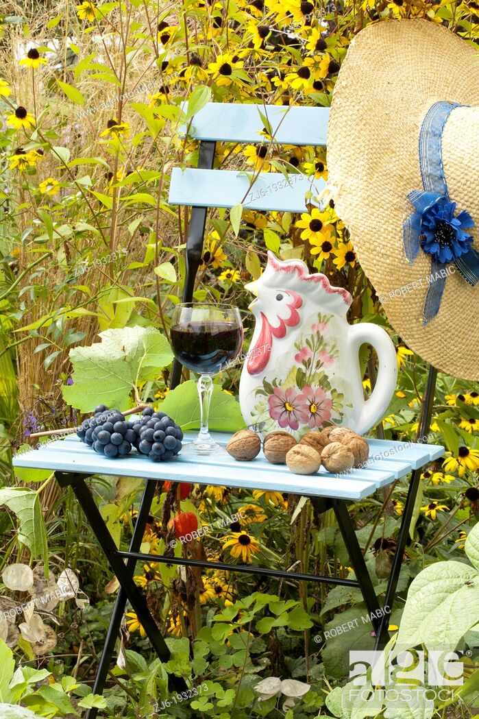 Stock Photo: Summer arrangements in the garden includes blue painted chair, glass of domestic Slovenian vine, grapes, straw hat, walnuts and pitcher.