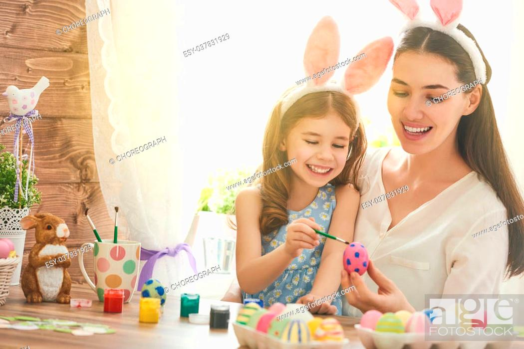 Stock Photo: Happy easter! A mother and her daughter painting Easter eggs. Happy family preparing for Easter. Cute little child girl wearing bunny ears on Easter day.