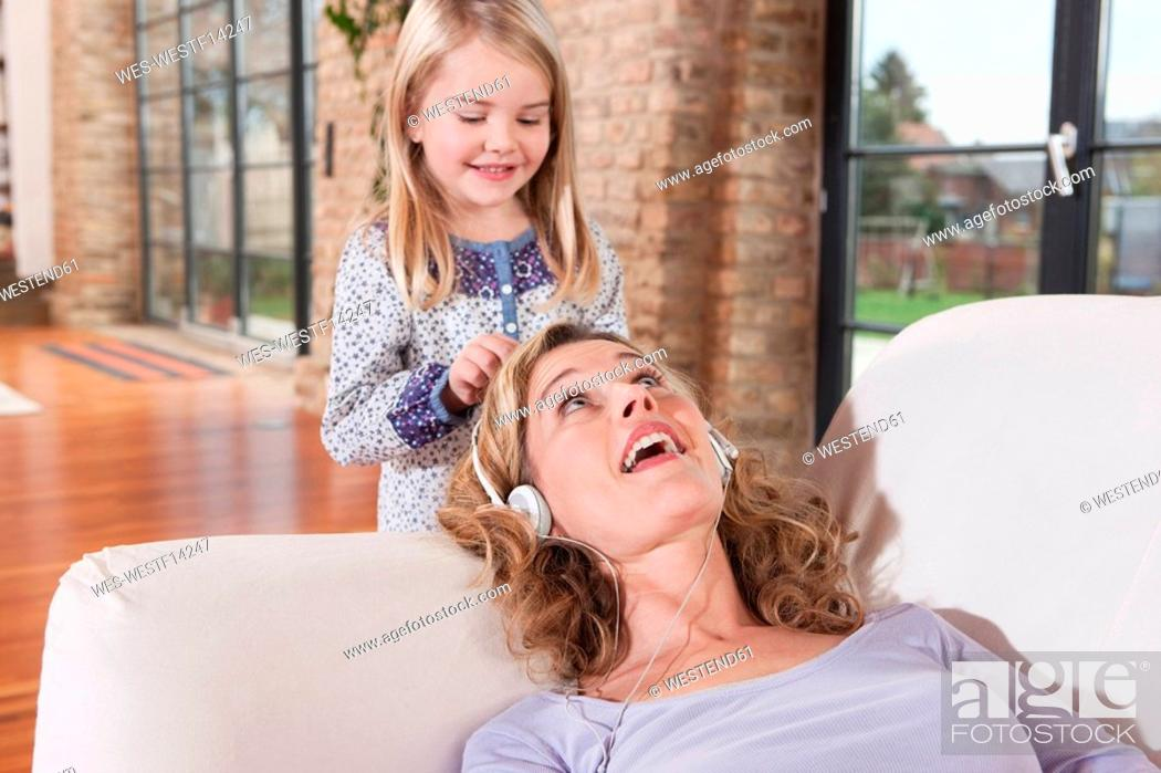 Stock Photo: Germany, Cologne, Mother and daughter 4-5, mother wearing headphones.