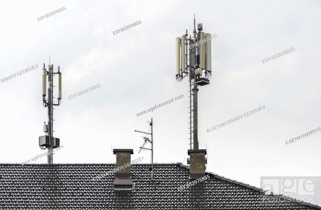 Stock Photo: 5G antennas on top of house. Antennas and transmitters on roof. High speed mobile internet concept.