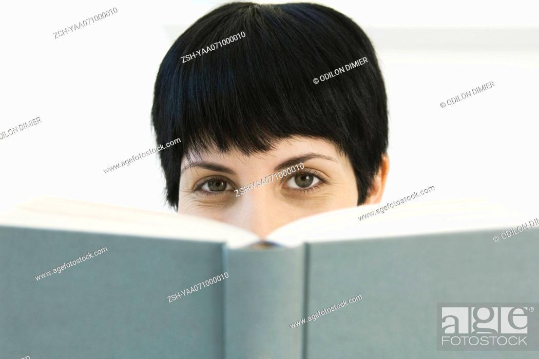 Stock Photo: Woman peering over book at camera.