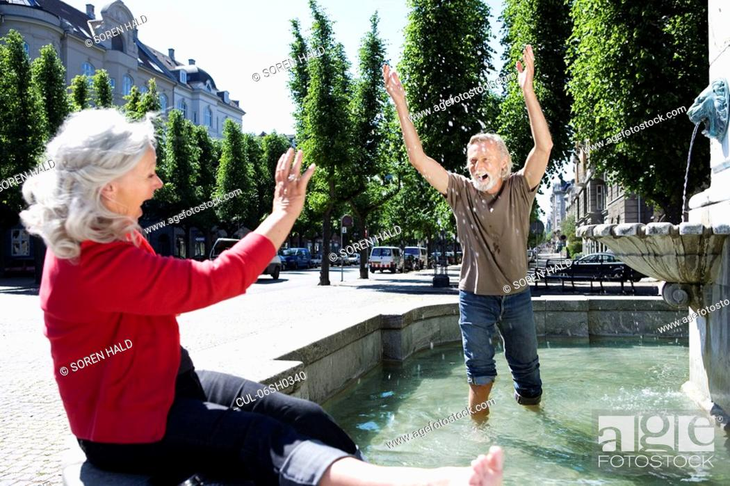 Stock Photo: Man throwing water at woman.