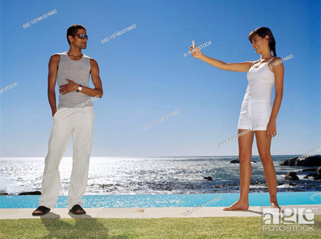 Stock Photo: Side profile of a young woman taking a photograph of a young man at the poolside.