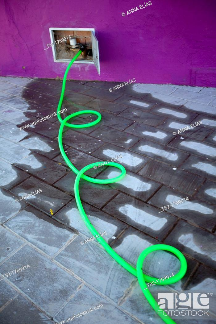 Stock Photo: twisted water hose out making green urban irrigation.