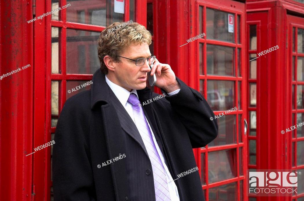 Stock Photo: Young businessman talking on a mobile phone next to a row of British red phone boxes.