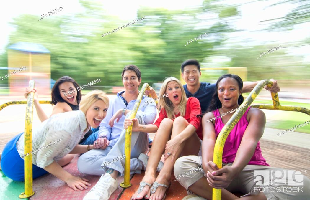 Stock Photo: mixed ethnic friends spinning on merry go round in playground laughing with black, vietnamese, hispanic, white people in their 20's and 30's MR-9, MR-5, MR-4.