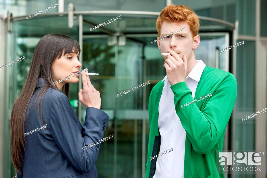 Stock Photo: Business executives smoking in front of an office building.