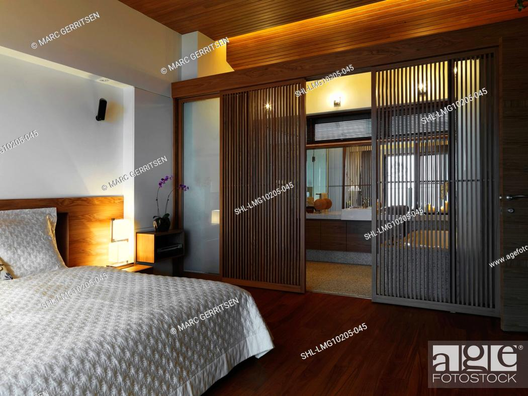 Stock Photo: Bedroom with white bed cover and hardwood floor.