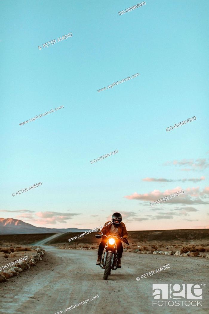 Stock Photo: Motorcyclist riding in desert, Trona Pinnacles, California, US.