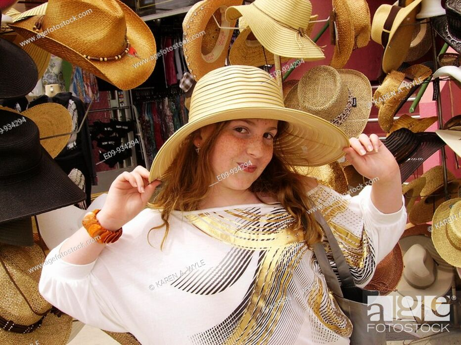 Stock Photo: 13-year-old girl with long blonde-brown hair and freckles trying on big hat in front of hat display on Venice Boardwalk, Venice, CA.