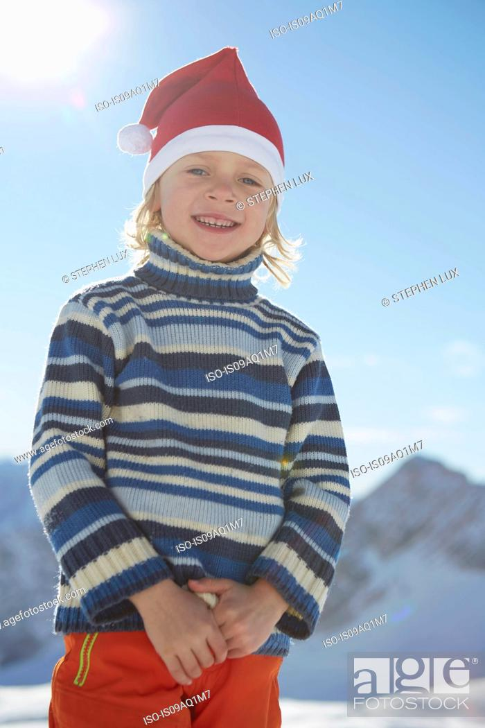 Stock Photo: Portrait of young boy in snowy landscape, wearing Santa hat.
