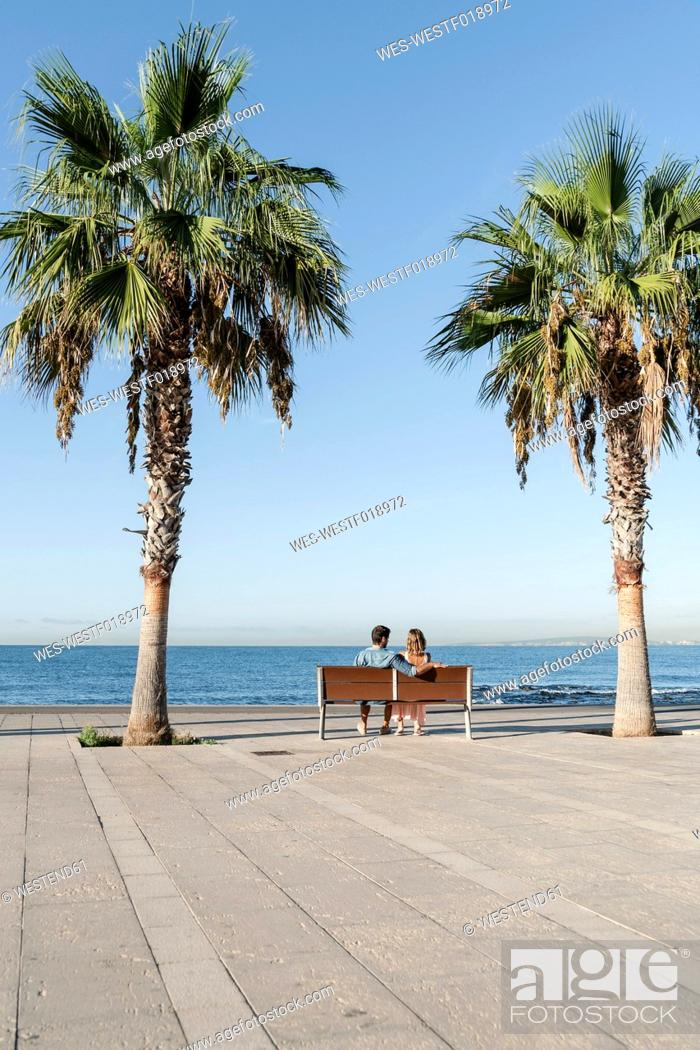 Stock Photo: Spain, Mid adult couple sitting on bench.