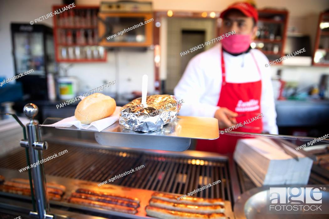 Stock Photo: 20 April 2020, Hamburg: Ali from the Lucullus snack bar on the Reeperbahn is only allowed to sell his curry sausage packed and to take away.