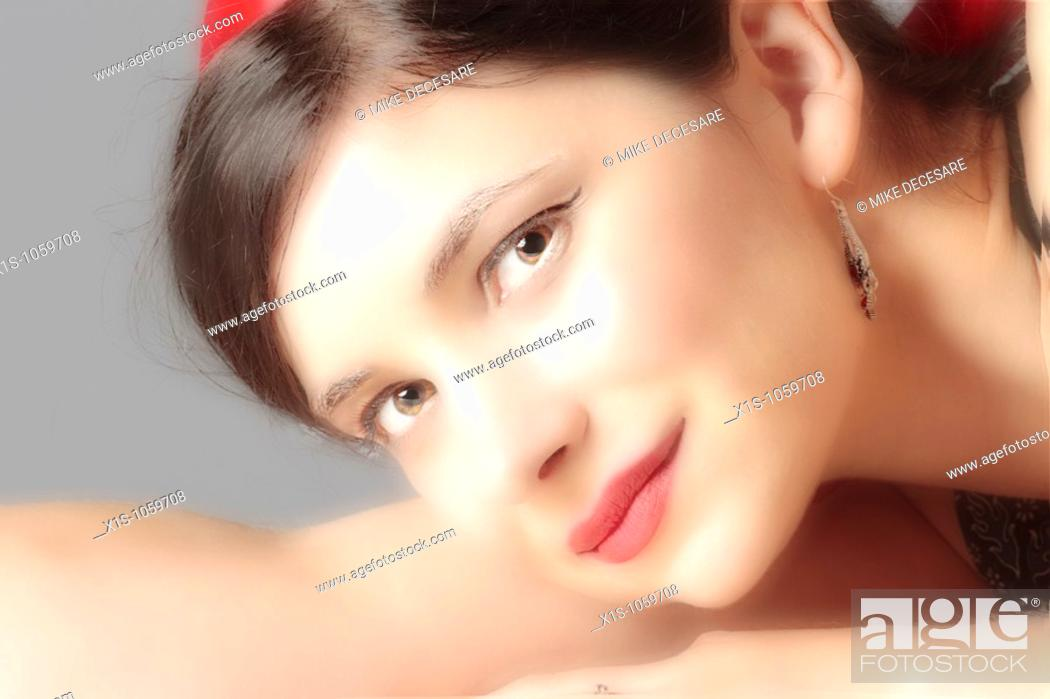 Stock Photo: Attractive young woman with her head in her arms looks toward the viewer.