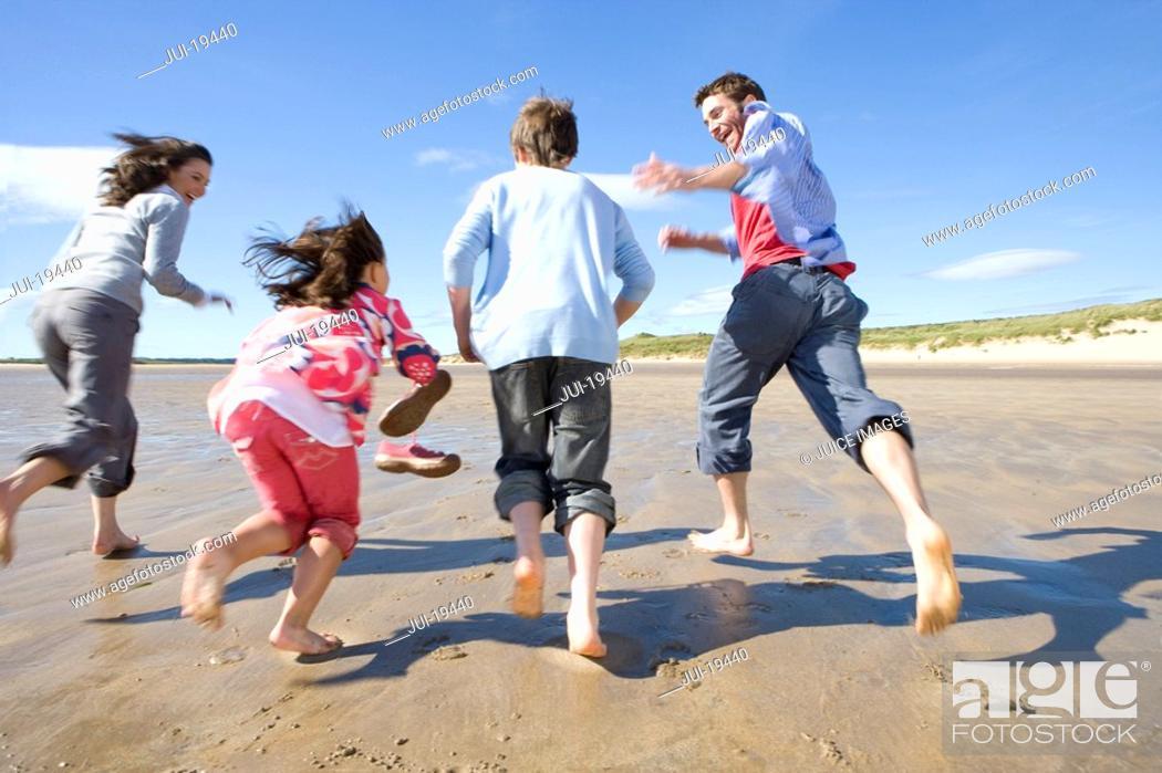 Stock Photo: Parents with children running on beach.