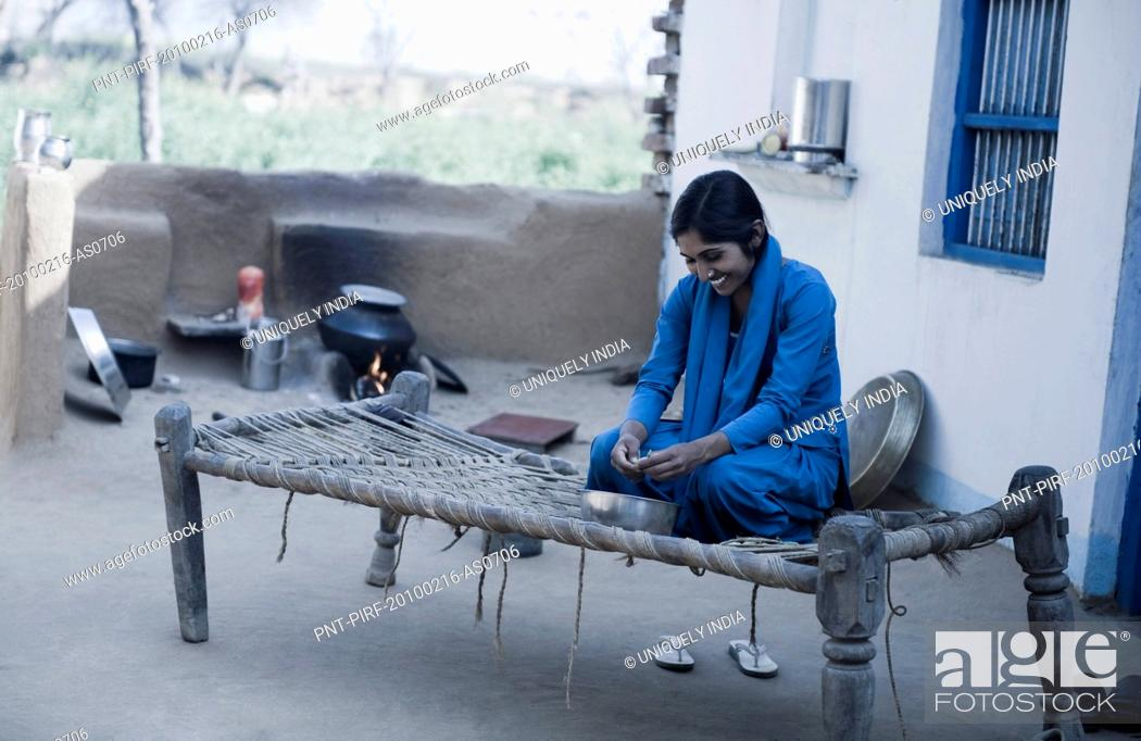 Stock Photo: Teenage girl shelling green peas, Farrukh Nagar, Gurgaon, Haryana, India.