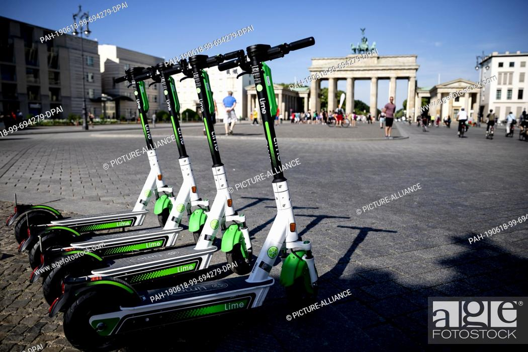 Imagen: 18 June 2019, Berlin: E- pedal scooters of the US-American company Lime stand in front of the Brandenburg Gate for rental.