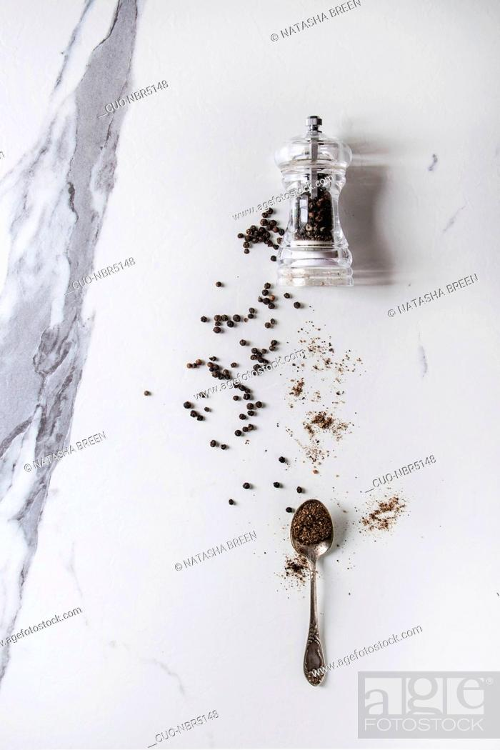 Stock Photo: Black peppers peppercorns and ground powder from transparent pepper mill to spoon over white marble texture background. Top view, space.