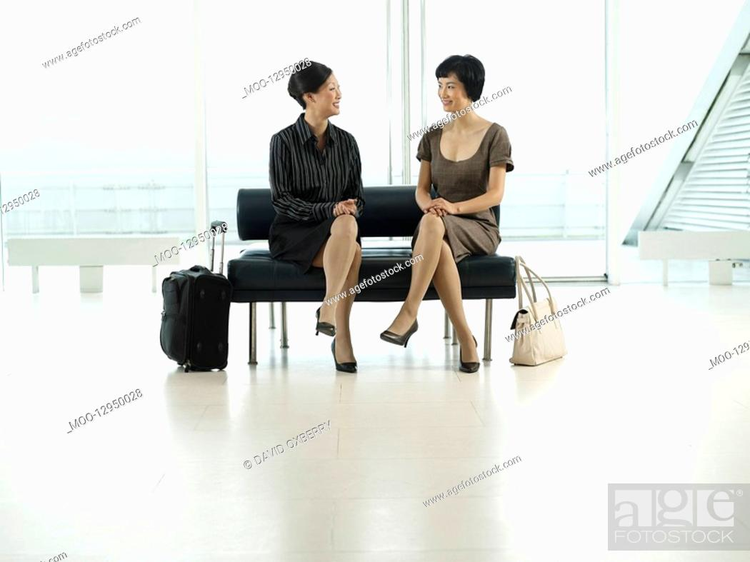 Stock Photo: Businesswomen Sitting legs crossed on Bench in airport before flight.