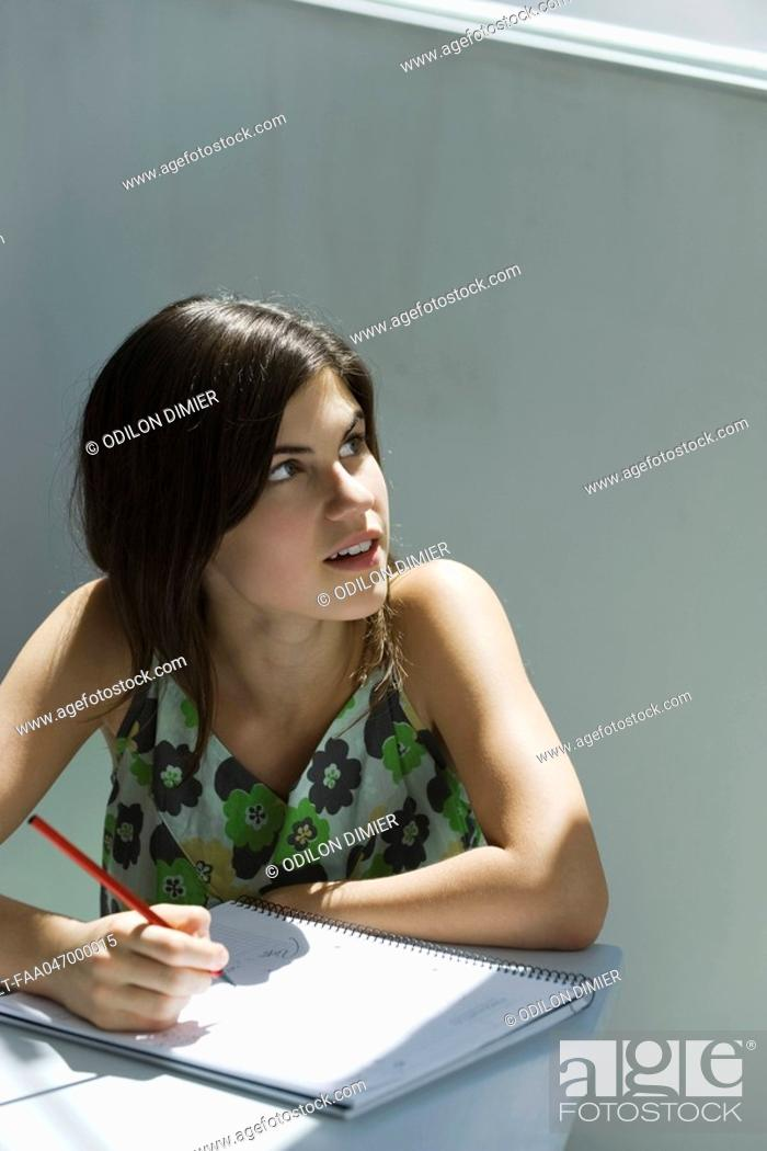 Stock Photo: Teenage girl with pen and notebook, looking over shoulder out window.