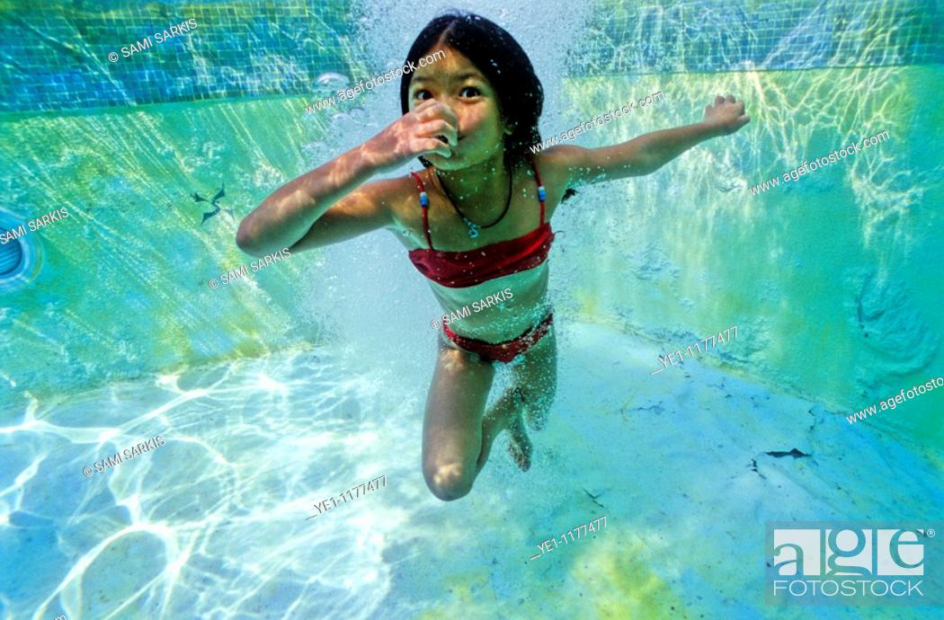 Stock Photo: Young girl holding her breath underwater in a swimming pool, Provence, France.